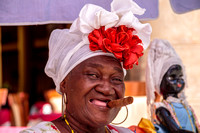 Old lady in colorful dress with Cuban Cigar